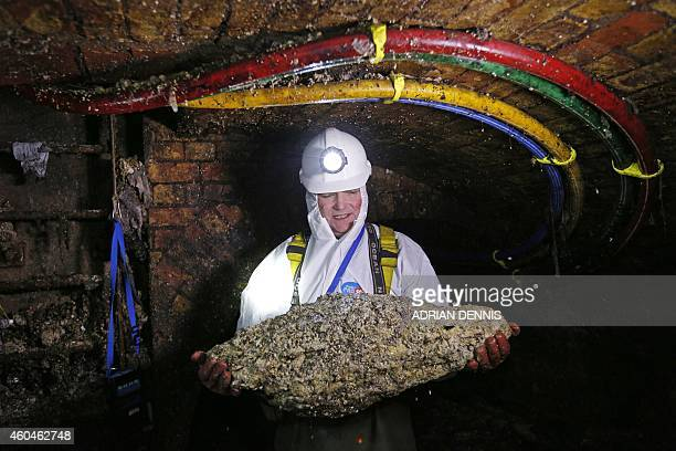 Tim Henderson a flusher or trunk sewer technician holds a fatberg as he works in the intersection of the Regent Street and Victoria sewer in London...