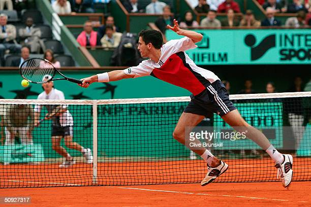 Tim Henman of Great Britain dives to return in his semi final match against Guillermo Coria of Argentina during Day Twelve of the 2004 French Open...