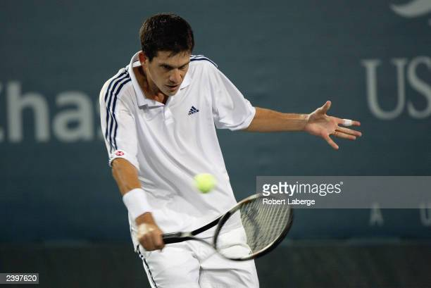 Tim Henman of Great Britain returns a shot to Juan Ignacio Chela of Argentina during the US Open at the United States Tennis Association National...