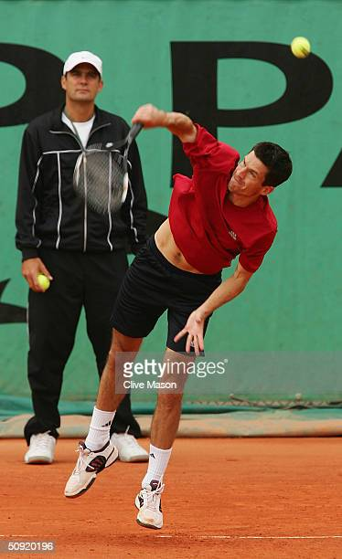 Tim Henman of Great Britain serves watched by his coach Paul Annacone in his practice session in preparation for his Semi final match against...