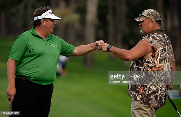 Tim Herron and Daniel Lawrence Whitney also known as 'Larry the Cable Guy' bump fists during the first round of the ATT Pebble Beach National ProAm...