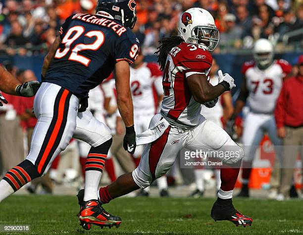 Tim Hightower of the Arizona Cardinals runs for yardage pursued by Hunter Hillenmeyer of the Chicago Bears at Soldier Field on November 8 2009 in...