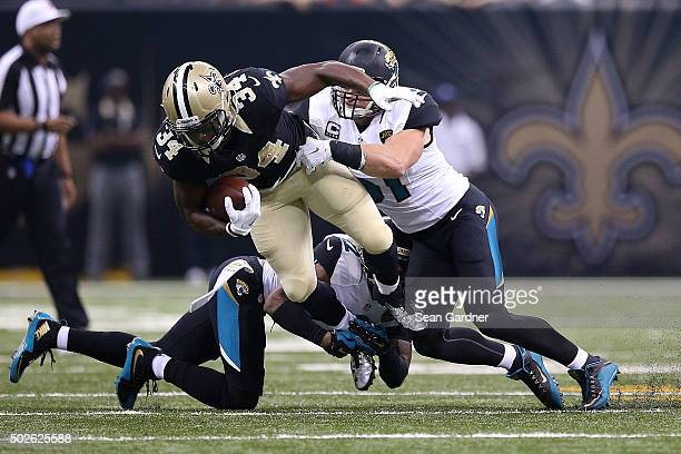 Tim Hightower of the New Orleans Saints is brought down by Aaron Colvin and Paul Posluszny of the Jacksonville Jaguars during the first quarter of a...