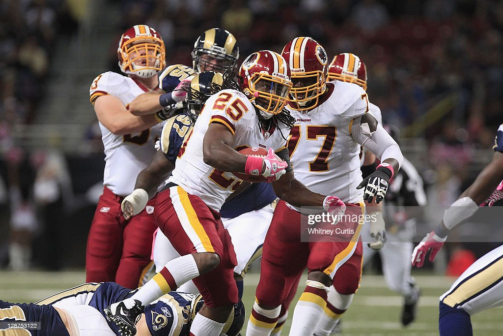 Tim Hightower #25 of the Washington Redskins advances the ball ahead of teammate Jammal Brown #77 against the St. Louis Rams October 2, 2011 at the Edward Jones Dome in St. Louis, Missouri.