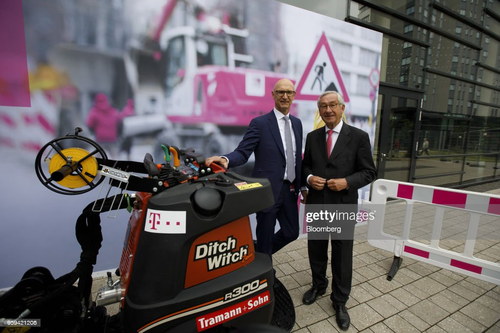 Tim Hoettges, chief executive officer of Deutsche Telekom AG, left, and Ulrich Lehner, chairman of Deutsche Telekom AG, pose for a photograph beside a Ditch Witch trenching machine, manufactured by Tramann & Sohn GmbH, during the company's shareholders' meeting in Bonn, Germany, on Thursday, May 17, 2018. Deutsche Telekom and Daimler AG agreed to settle a 14-year-old arbitration case with the German government over the countrys truck toll system with a cash payment of 1.1 billion euros, the Transport Ministry said in a statement. Photographer: Alex Kraus/Bloomberg via Getty Images