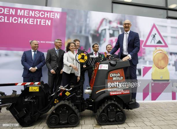 Tim Hoettges chief executive officer of Deutsche Telekom AG right stands on the driving platform of a Ditch Witch trenching machine manufactured by...