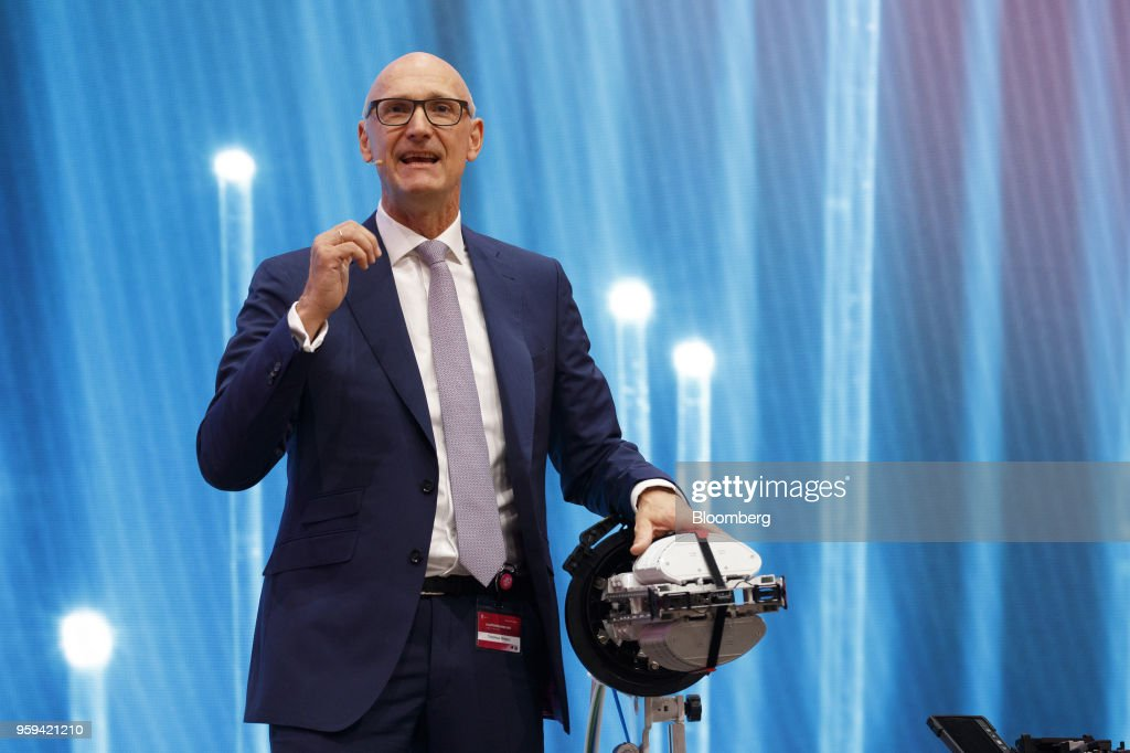 Tim Hoettges, chief executive officer of Deutsche Telekom AG, speaks beside fiber cable splicing machine during the company's shareholders' meeting in Bonn, Germany, on Thursday, May 17, 2018. Deutsche Telekom and Daimler AG agreed to settle a 14-year-old arbitration case with the German government over the countrys truck toll system with a cash payment of 1.1 billion euros, the Transport Ministry said in a statement. Photographer: Alex Kraus/Bloomberg via Getty Images