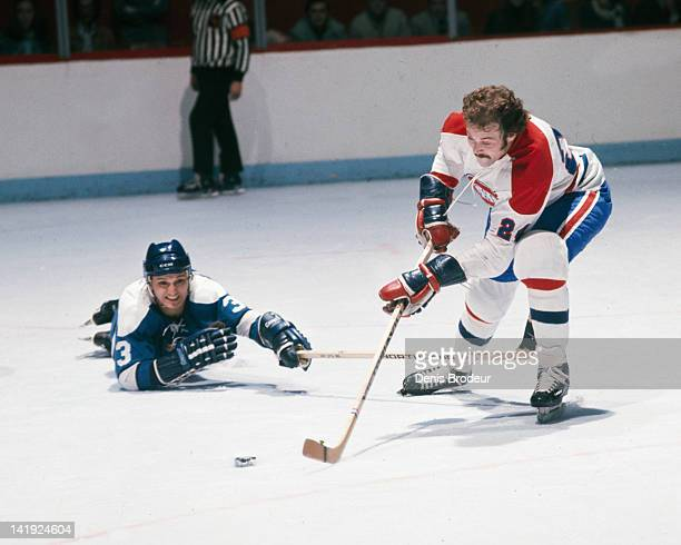 Tim Horton of the Pittsburgh Penguins dives for the puck as Chuck Lefley of the Montreal Canadiens skates towards the net Circa 1970 at the Montreal...
