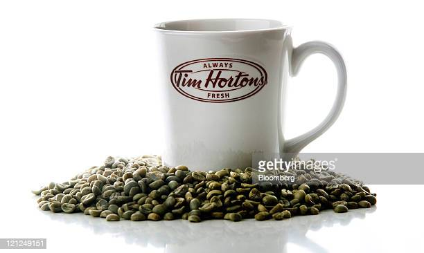 A Tim Hortons Inc mug and coffee beans are arranged for a photograph in Ancaster Ontario Canada on Monday Aug 15 2011 Tim Hortons Inc the...