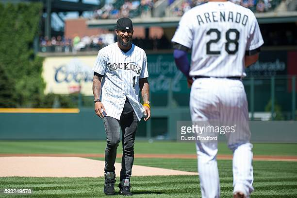 Tim Howard goalie of the Colorado Rapids smiles at Nolan Arenado of the Colorado Rockies after throwing out a ceremonial first pitch before a game...
