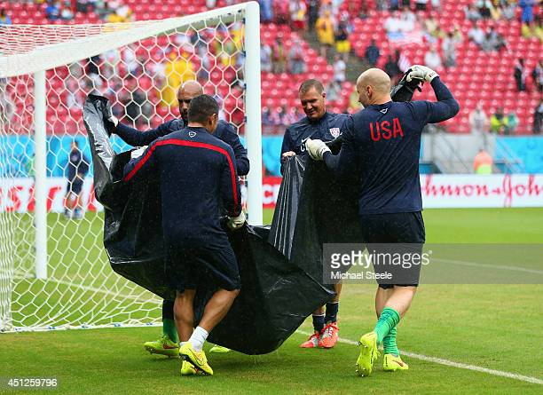 Tim Howard , goalkeeper coach Chris Woods and Brad Guzan of the United States move a water-filled tarp prior to the 2014 FIFA World Cup Brazil group...