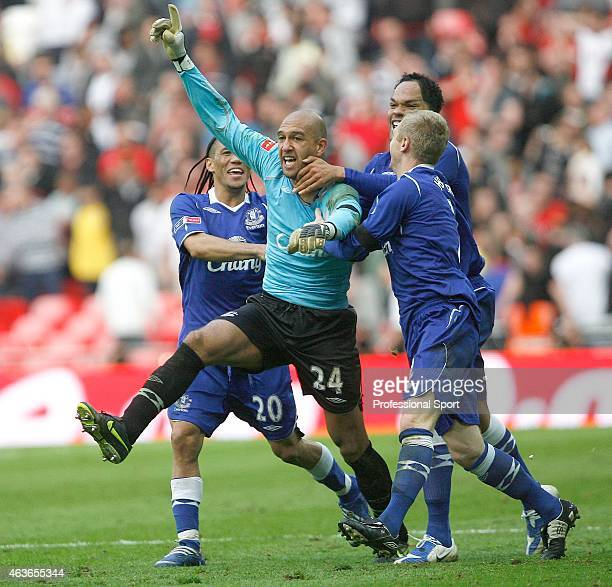 Tim Howard of Everton celebrates with teammates Tony Hibbert Joleon Lescott and Steven Pienaar after victory in the penalty shoot out during the FA...