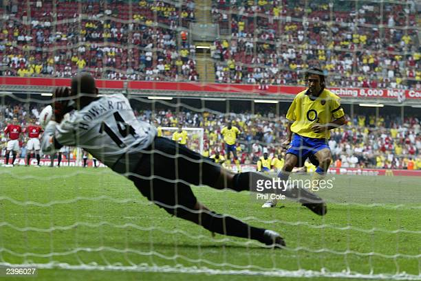 Tim Howard of Manchester United saves the final penalty from Robert Pires of Arsenal during the FA Community Shield match between Arsenal and...