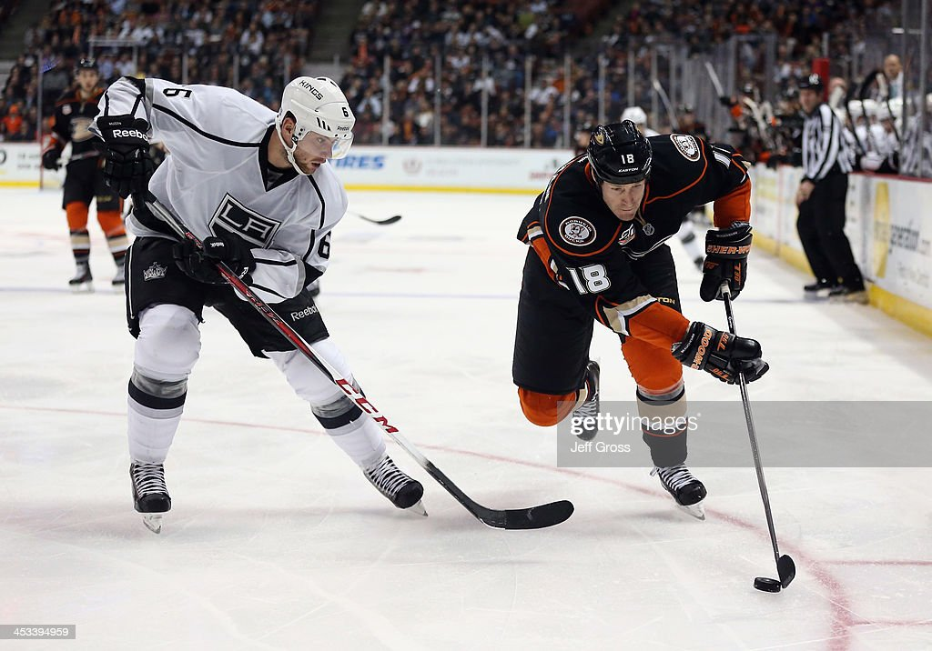 Tim Jackman #18 of the Anaheim Ducks is pursued by Jake Muzzin #6 of the Los Angeles Kings for the puck in the third period at Honda Center on December 3, 2013 in Anaheim, California. The Kings defeated the Ducks 3-2 in a shootout.
