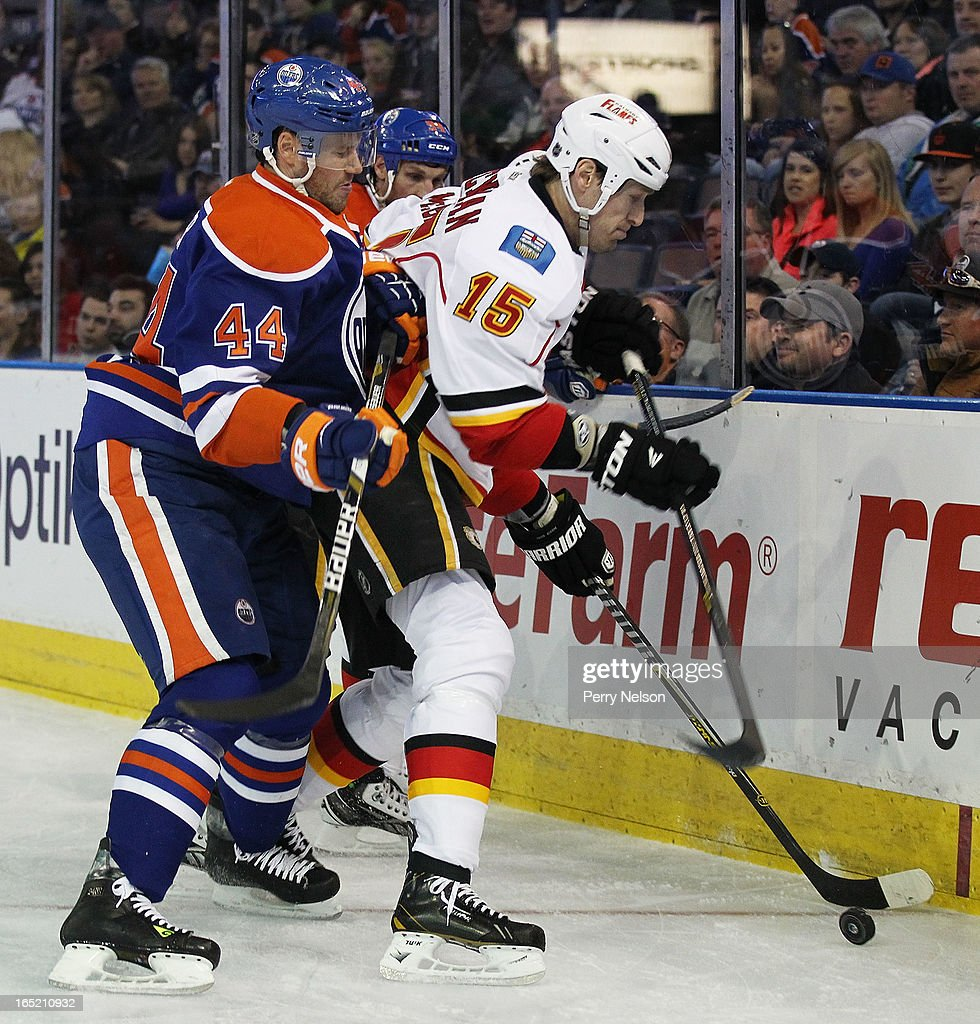 Tim Jackman #15 of the Clagery Flames protects the puck against Corey Potter #44 of the Calgary Flames at Rexall Place on April 1, 2013 in Edmonton, Alberta, Canada.