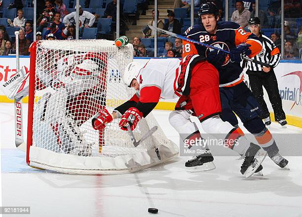Tim Jackman of the New York Islanders tries to get past Aaron Ward of the Carolina Hurricanes on October 21 2009 at Nassau Coliseum in Uniondale New...