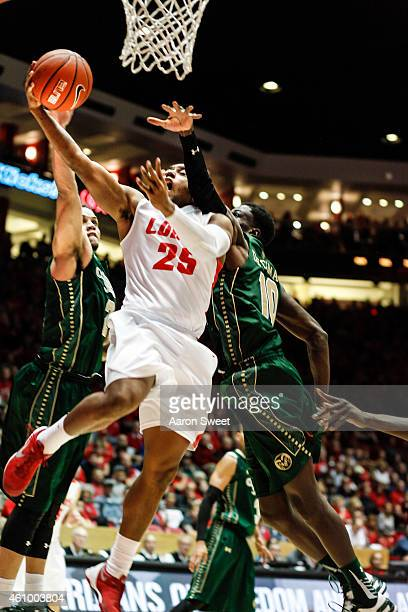Tim Jacobs of the New Mexico Lobos drives to the basket against Joe De Ciman #10 and JJ Avila of the Colorado State Rams during their game at The...