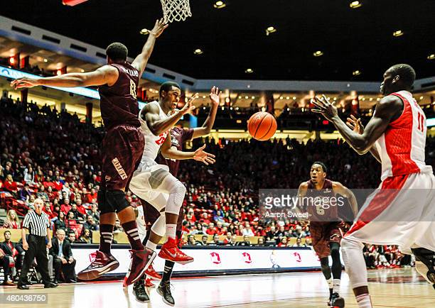 Tim Jacobs of the New Mexico Lobos passes to teammate Obij Aget as Marvin Williams of the LouisianaMonroe Warhawks defends during their game at The...