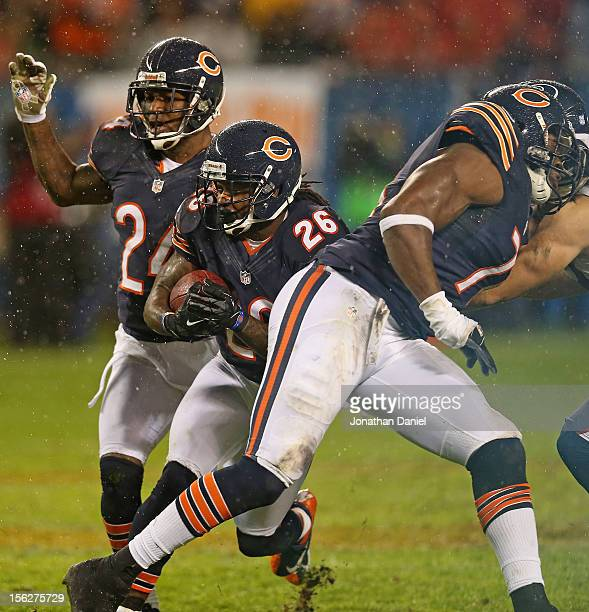Tim Jennings of the Chicago Bears returns an interception between teammates Kelvin Hayden and Israel Idonije against the Houston Texans at Soldier...