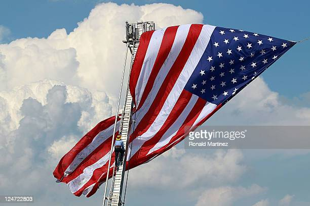 Tim Jones a volunteer firefighter unfurls the American flag before the season opener between the New York Giants and the Washington Redskins at...