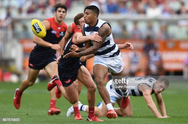 Tim Kelly of the Cats handballs whilst being tackled by Bayley Fritsch of the Demons during the round one AFL match between the Melbourne Demons and...