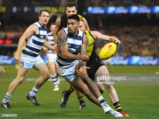 Tim Kelly of the Cats handballs whilst being tackled by Nick Vlastuin of the Tigers during the round 13 AFL match between the Geelong Cats and the...