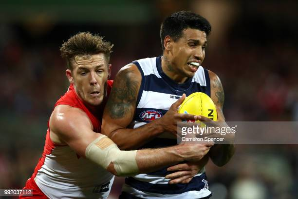 Tim Kelly of the Cats is tackled by Luke Parker of the Swans during the round 16 AFL match between the Sydney Swans and the Geelong Cats at Sydney...