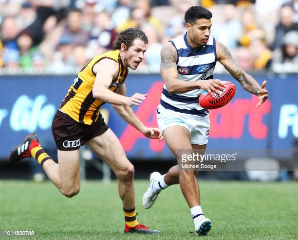 Tim Kelly of the Cats runs with the ball Isaac Smith of the Hawks during the round 21 AFL match between the Hawthorn Hawks and the Geelong Cats at...