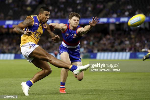 Tim Kelly of the Eagles kicks the ball ahead of Taylor Duryea of the Bulldogs during the 2021 AFL Round 02 match between the Western Bulldogs and the...