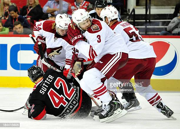 Tim Kennedy, Keith Yandle and Derek Morris of the Phoenix Coyotes drive Brett Sutter of the Carolina Hurricanes to the ice as they battle for a loose...