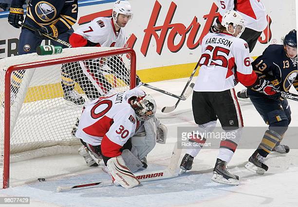 Tim Kennedy of the Buffalo Sabres watches his shot slide past Brian Elliott and Erik Karlsson of the Ottawa Senators and into the net for a goal at...