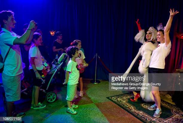 Tim Kircher left of Lincoln Calif takes a photo of Cruella de Vil and his wife Julie inside the Conjure a Villain show at Disneyland's Halloween in...