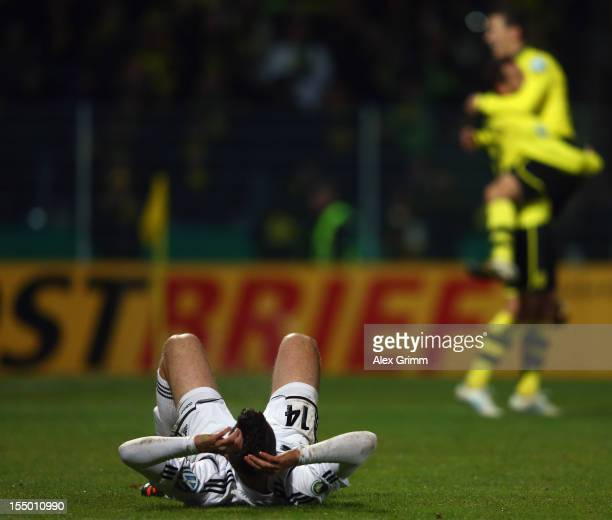 Tim Kister of Aalen reacts as Julian Schieber of Dortmund celebrates his team's fourth goal with team mate Ivan Perisic during the second round match...