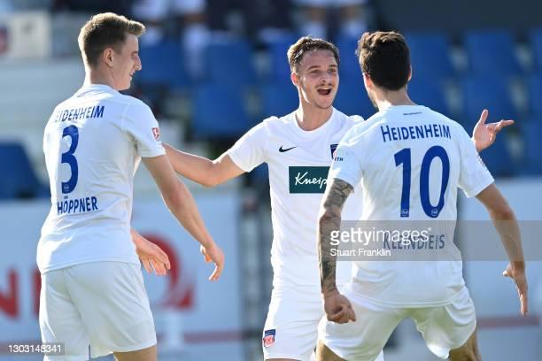 Tim Kleindienst of 1. FC Heidenheim 1846 celebrates with teammates Jan Schoeppner and Marvin Lee Rittmueller after scoring his team's first goal...