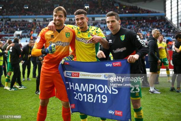 Tim Krul, Ben Godfrey and KennyMcLean of Norwich City celebrate winning the title after the Sky Bet Championship match between Aston Villa and...