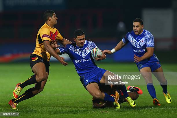 Tim Lafai of Samoa is halted by Nene McDonald of Papua New Guinea during the Rugby League World Cup Group B match between Papua New Guinea and Samoa...