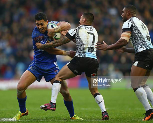 Tim Lafai of Samoa is held up by Aaron Groom and Waisale Ligani Naiqama of Fiji during the Rugby League World Cup Quarter Final match between Samoa...