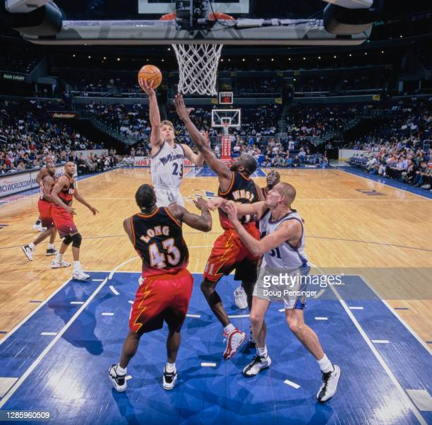Tim Legler, Shooting Guard for the Washington Wizards makes a one handed lay up for the basket as Grant Long and Mark West of the Atlanta Hawks...