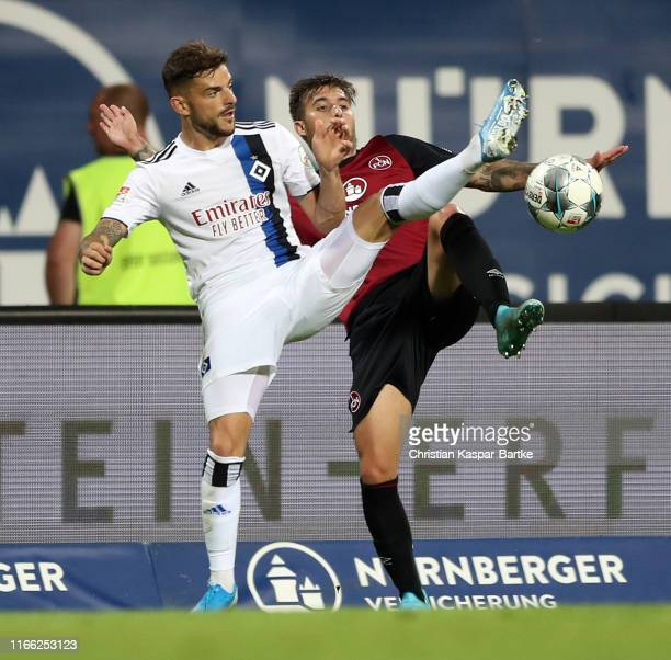 Tim Leibold of Hamburg is challenged by Iuri Medeiros during the Second Bundesliga match between 1. FC Nuernberg and Hamburger SV at...
