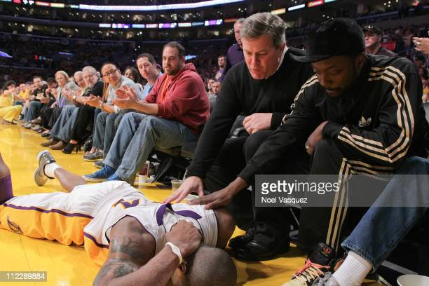 Tim Leiweke and william tend to Kobe Bryant after suffering a neck injury at game between the New Orleans Hornets and the Los Angeles Lakers at...