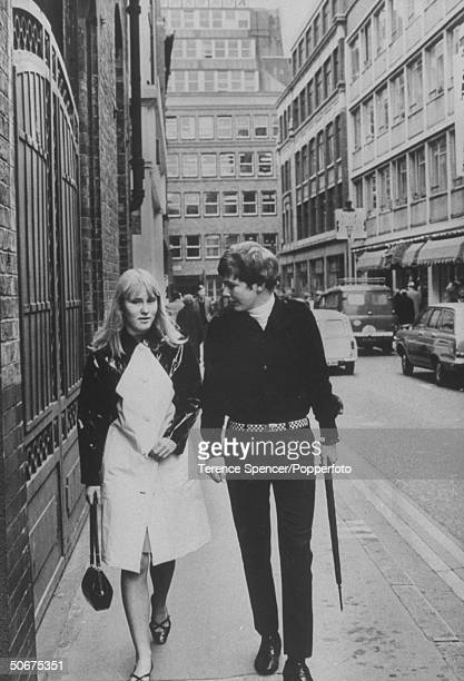 Tim Lepage is walking down Carnaby St with a young lady while wearing dark pants and shirt checked belt and an umbrella in his hand