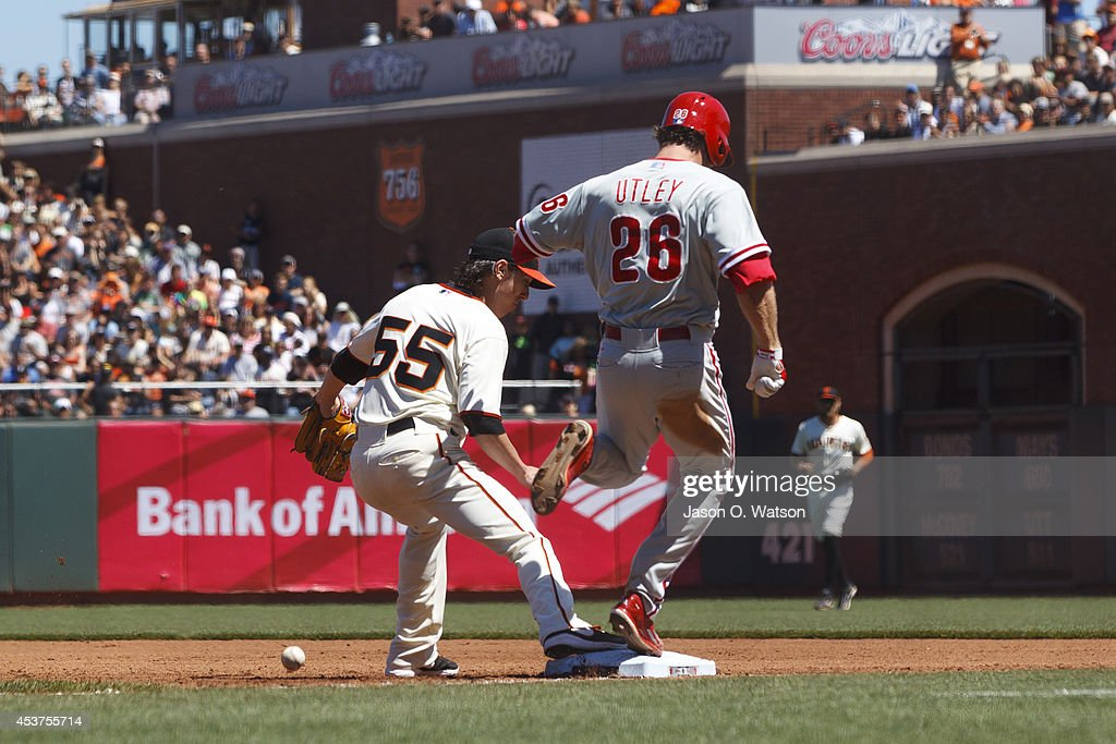 Tim Lincecum #55 of the San Francisco Giants is unable to complete a double play after dropping the ball at first base in front of Chase Utley #26 of the Philadelphia Phillies during the fourth inning at AT&T Park on August 17, 2014 in San Francisco, California.