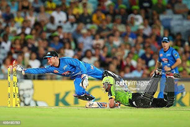 Tim Ludeman of the Strikers attempts to run out Mike Hussey of the Thunder during the Big Bash League match between Sydney Thunder and the Adelaide...