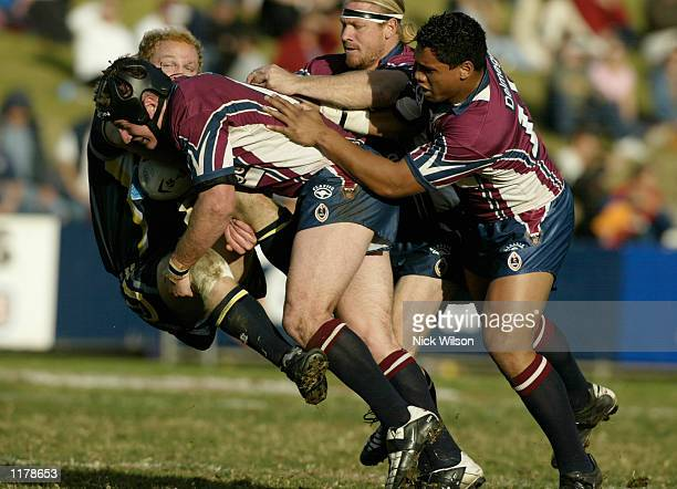 Tim Maddison of the Cowboys is tackled by the Eagles defence during the round 20 NRL match between the Northern Eagles and the North Queensland...