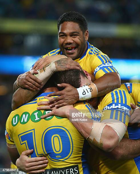 Tim Mannah of the Eels celebrates with his team mates Chris Sandow and Brad Takairangi of the Eels after scoring a try during the round 17 NRL match...