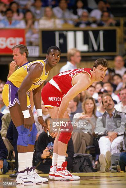 Tim McCormick of the Houston Rockets waits at the line with Orlando Woolridge of the Los Angeles Lakers during a game in the198990 season at the...