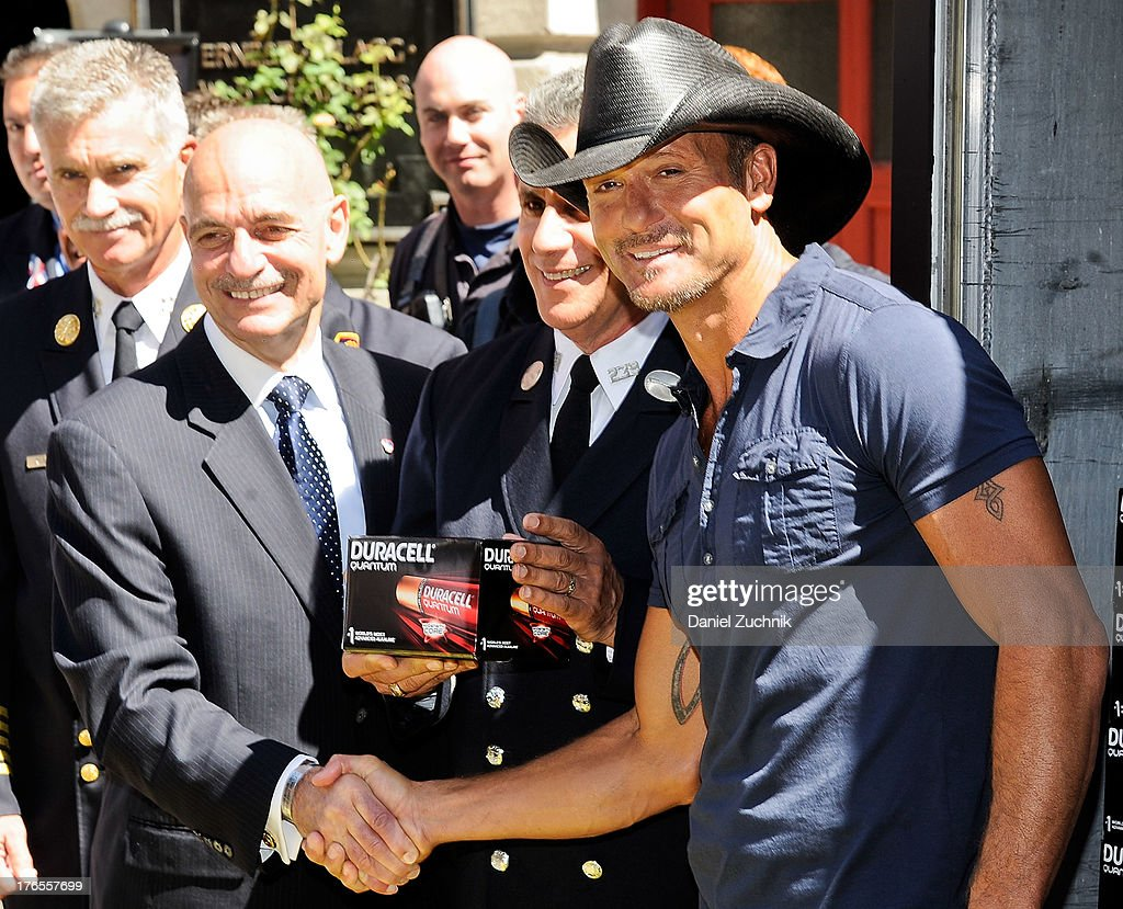Tim McGraw and New York Fire Commissioner Salvatore Cassano (L) attend the 'Quantum Heroes' premiere at Engine 33, Ladder 9 on August 15, 2013 in New York City.