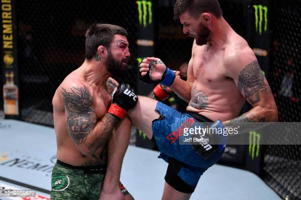 Tim Means knees Mike Perry in their welterweight bout during the UFC 255 event at UFC APEX on November 21, 2020 in Las Vegas, Nevada.