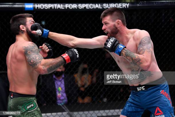 Tim Means punches Mike Perry in their welterweight bout during the UFC 255 event at UFC APEX on November 21, 2020 in Las Vegas, Nevada.