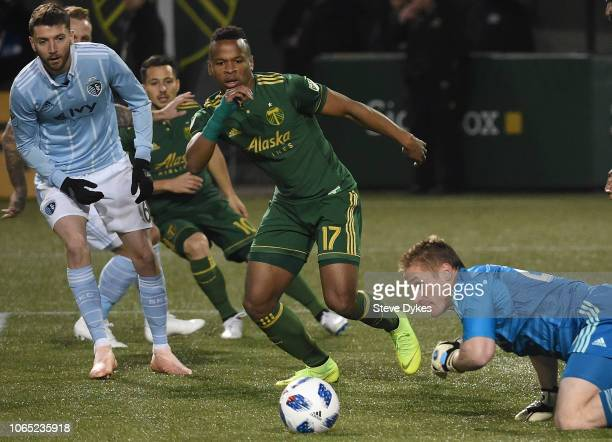 Tim Melia of Sporting Kansas City goes after a ball as Jeremy Ebobisse of Portland Timbers closes in during the first half of the match at Providence...
